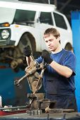 stock photo of levers  - automotive mechanic worker tighten screw with spanner during automobile car maintenance at lever repair service station - JPG