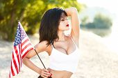 picture of independent woman  - Sexy brunette woman holding USA flag outdoor independence day - JPG