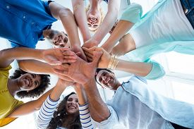 foto of huddle  - Creative team putting their hands together in circle - JPG