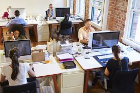 image of fifties  - Wide Angle View Of Busy Design Office With Workers At Desks - JPG