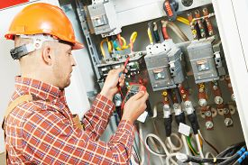 picture of labor  - adult electrician builder engineer worker with electric scheme plan in front of fuse switch board - JPG