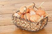 foto of chicken-wire  - Basket of freshly laid eggs in wire basket on wooden background - JPG
