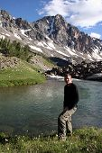 stock photo of beartooth  - day hiker poses in front of the rock creek with whitetail peak in the background - JPG