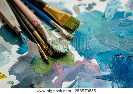 poster of Artist Paint Brushes On Wooden Palette. Texture Mixed Oil Paints In Different Colors. Instruments To