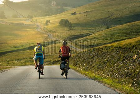 poster of Cycling in countryside in summer. Lifestyle concept. Two man cycling in sunset in countryside. Lifestyle. Travel cycling in sunset in countryside hills. Cyclists travelers on the road in sunset. Lifestyles. Cycling. Bicycle. Sunset. Travel
