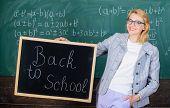 Beginning Of New School Season. Woman Teacher Formal Suit Holds Blackboard Inscription Back To Schoo poster