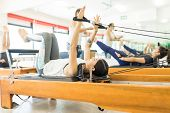 Young Woman Pulling Resistance Bands While Lying On Reformer Machine At Gym poster
