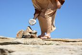 foto of adultery  - Man standing in the sun on sandy rocks holding a rock depicting ansswer by Jesus from John Chapter 8 - JPG