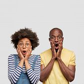 Vertical Shot Of Stupefied African American Male And Female Stare At Camera With Great Surprisement, poster