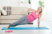 Working With Your Body. Full Length Of Beautiful Middle Aged Woman In Sportswear Doing Plank While S poster