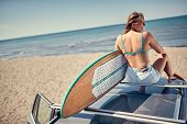 Extreme Sport. Surfing. Smiling surfer girl sitting on the car and getting ready for surfing. Back v poster