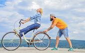 Man Helps Keep Balance And Ride Bike. How To Learn To Ride Bike As Adult. Girl Cycling While Boyfrie poster