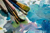 Artist Paint Brushes On Wooden Palette. Texture Mixed Oil Paints In Different Colors. Instruments To poster