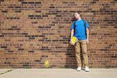 Student leaning his head on a brick wall at school poster