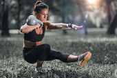 Outdoor Exercising. Female Athlete Exercising With Kettlebell In The Park. poster