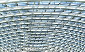 picture of purlin  - Curved reinforced steel roof joists in a conservatory roof with glass panes in between and blue sky beyond - JPG