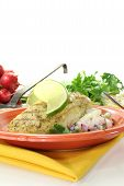 stock photo of hake  - Hake with lemon slice parsley chives and potato salad on a light background - JPG