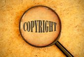 image of plagiarism  - Magnifying glass focused on the word copyright - JPG