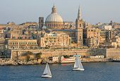 stock photo of carmelite  - Two Yachts sailing by a harbour in Malta - JPG