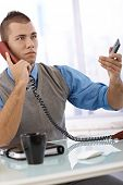 Determined businessman on landline phone call in office, with mobile phone handheld.