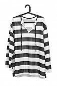 A studio shot of a black and white striped prison uniform on a hanger isolated against white backgro