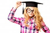 Portrait of a cute ten years girl in big round spectacles and academic hat. Isolated over white.
