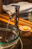 stock photo of spigot  - Tap flowing in a luxurious hotel room bathroom - JPG