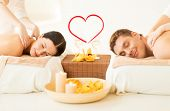spa, beauty, love and happiness concept - smiling couple with candles, flowers and champagne glasses
