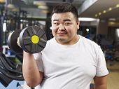 Overweight Man Exercising In Gym