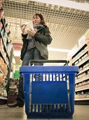 Woman Shopping With Blue Basket At Supermarket Shop. Retail.