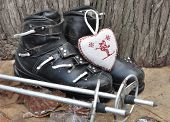 picture of ski boots  - old ski boots in a rustic setting with a heart shaped cushion - JPG