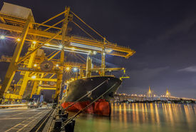 image of shipyard  - Landscape of Container Cargo freight ship with working crane bridge in shipyard at dusk for Logistic Import Export background - JPG