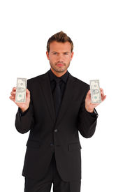 stock photo of holding money  - Young businessman holding money against white background - JPG