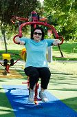 stock photo of lats  - Mature woman training on a Lat Pull machine at outdoor fitness circuit in the green sunny park  - JPG