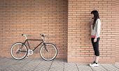 picture of sportive  - Beautiful young sportive woman posing with custom fixie bike over a orange brick wall on the background - JPG
