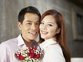 picture of fiance  - portrait of happy young couple smiling with flowers - JPG
