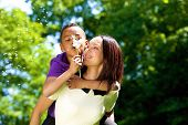 stock photo of dandelion  - Close up portrait of a happy young mother with son piggybacking and blowing dandelion - JPG
