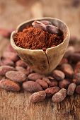 image of cocoa beans  - cocoa powder in spoon on roasted cocoa chocolate beans background - JPG
