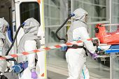 stock photo of stretcher  - Hazardous material medical team with stretcher entering contaminated building - JPG