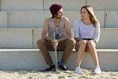 picture of conversation  - young couple sitting on large concrete steps - JPG