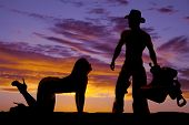 image of begging  - A silhouette of a woman on her hands and knees begging her cowboy - JPG