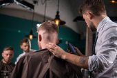 image of clippers  - hairdresser  cuts    hair  with hair clipper on back of the head of handsome satisfied  client in  professional  hairdressing salon low angle - JPG