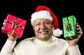 image of coy  - Honorable old man with Santa Claus cap his showing a red and a green wrapped present - JPG
