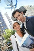 stock photo of broadway  - Tourists on Broadway street reading city guide - JPG