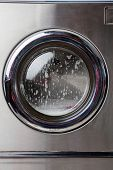 stock photo of suds  - Closeup of washing machine with foam on front load - JPG