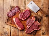 image of cutting board  - Different types of Raw fresh meat Steaks and meat cleaver on cutting board on wooden background - JPG