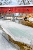 image of covered bridge  - The historic red Oakalla Covered Bridge crosses a snowy and partially frozen Big Walnut Creek in rural Putnam County Indiana  - JPG