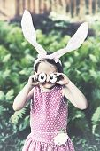 picture of bunny ears  - A funny portrait of a girl having fun on Easter wearing bunny ears and holding up silly eyes made from eggs outside in a garden during the spring season - JPG