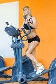 pic of elliptical  - Young sports woman doing exercises on an elliptical trainer in the gym - JPG