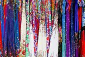 foto of stall  - Rows of colourful silk scarfs hanging at a market stall in Thailand - JPG